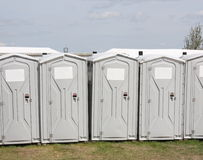 Portable Toilet Row. A row of portable toilets with blank labels ready for your text Stock Photos