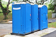 Portable Toilets. Three Blue Color Portable Toilet In The Park For Public Use royalty free stock photos
