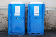 Portable toilets. Two blue portable toilet cabins at construction site Stock Image