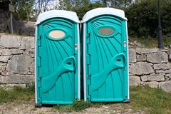 Portable toilets for men and women. Separated modern design portable toilets for men and women in front of traditional stone wall and grass area Stock Image