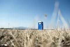 Portable toilette cabin. In a field stock image