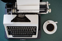 Portable typewriter, circa 1970. Portable metal typewriter, circa 1970, on a green desk in its open carrying case with a cup of coffee to the right.  May be used Royalty Free Stock Images