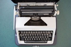 Portable typewriter, circa 1970. Portable metal typewriter, circa 1970, on a green desk in its open carrying case.  May be used to symbolize journalism or Royalty Free Stock Photo