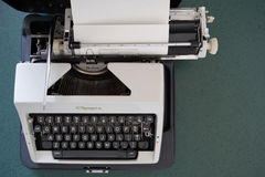 Portable typewriter, circa 1970. Portable metal typewriter, circa 1970, on a green desk in its open carrying case with a sheet of parchment paper loaded and Royalty Free Stock Photo