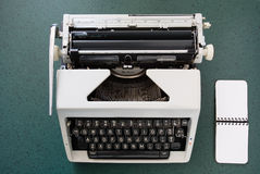 Portable typewriter, circa 1970, with notepad Stock Photo