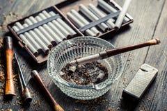 Portacenere di vetro con i tubi di legno sottili, sigarette Immagini Stock