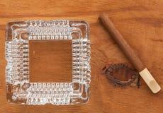 Portacenere di vetro con il sigaro su una superficie di legno Fotografia Stock