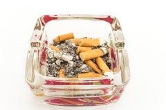 Portacenere di vetro con le estremità di sigaretta, isolate su bianco Immagini Stock