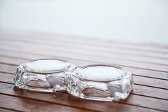 Portacenere di vetro inutilizzato sottosopra sulla tavola o sul banco di legno al balcone Progettazione interna della decorazione immagini stock
