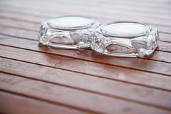 Portacenere di vetro inutilizzato sottosopra sulla tavola o sul banco di legno al balcone Progettazione interna della decorazione fotografia stock