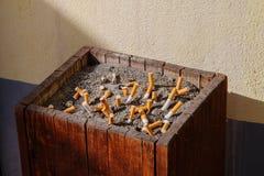 Portacenere di Woodden con la sabbia piena delle sigarette affumicate Immagine Stock