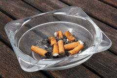 Portacenere e sigarette su fondo di legno Immagini Stock