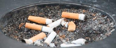 Portacenere nero sporco con le sigarette affumicate Fotografia Stock