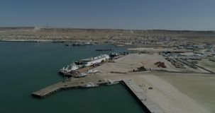 portacontenedores 4K - fijos en el puerto de Bautino Kazajistán en las orillas del mar Caspio Carga y descarga almacen de video