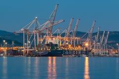 Portacontenedores se está descargando en el puerto marítimo internacional de Koper tarde en la noche fotos de archivo libres de regalías