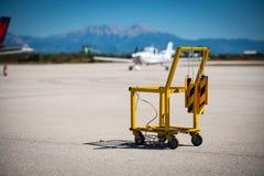 Portador de las cuñas de un avión del amarillo y del extintor en un pequeño aeropuerto foto de archivo