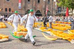 Portadores que caminan con muchos quesos en el mercado famoso de Alkmaar fotos de archivo libres de regalías