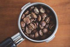 Portafilter com close-up dos feijões de café fotos de stock