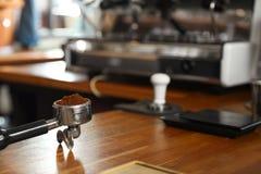 Portafilter con caffè macinato sul contatore nella barra immagine stock libera da diritti