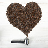 Portafilter handle and heart shaped rammer with arabica seeds. A portafilter handle and a heart shaped rammer with arabica seeds. Composition Royalty Free Stock Images