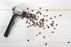 Portafilter handle with scattered coffee beans on wooden surface in top view Royalty Free Stock Images
