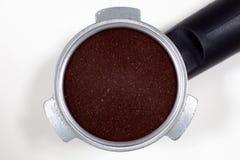 Portafilter llenó del café molido en un fondo blanco Fotos de archivo libres de regalías