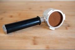 Portafilter z temping zmieloną kawę na drewnianym stole Fotografia Stock
