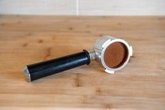 Portafilter z temping zmieloną kawę na drewnianym stole Zdjęcia Royalty Free