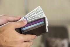 Portafoglio con 100 banconote in dollari in una mano del ` s dell'uomo Fotografie Stock Libere da Diritti