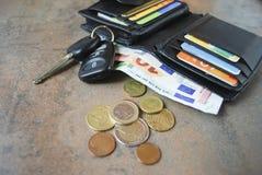 Portafoglio con contanti, carte, chiavi dell'automobile sulla tavola Fotografia Stock