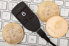 Portafoglio dell'hardware di Trezor per il cryptocurrency sulla tastiera con le monete dorate fotografia stock libera da diritti