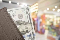 Portafoglio di cuoio con 100 banconote in dollari sopra fondo variopinto Immagini Stock Libere da Diritti