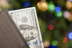 Portafoglio di cuoio con 100 banconote in dollari sopra fondo variopinto Fotografia Stock