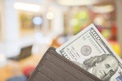 Portafoglio di cuoio con 100 banconote in dollari sopra fondo variopinto Fotografia Stock Libera da Diritti