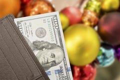 Portafoglio di cuoio con 100 banconote in dollari sopra fondo variopinto Immagini Stock