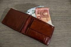 Portafoglio di cuoio in pieno di euro banconota su una tavola di legno decorata immagini stock libere da diritti