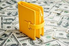 Portafoglio giallo che riposa sopra molto cento dollari Fotografia Stock Libera da Diritti