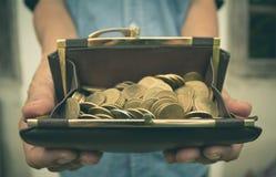 Portafoglio maschio della tenuta con le monete di oro dei soldi in sua mano Fotografia Stock