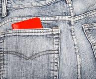 Portafoglio rosso in una tasca posteriore delle blue jeans Immagine Stock