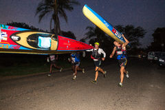 Portage Running Canoe Marathon. Athletes running with their canoes in the early Morning start of the Non Stop Dusi canoe marathon. Photo image captures the Royalty Free Stock Images