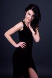 Portait молодой красивой сексуальной женщины в черном платье над серым цветом Стоковые Изображения