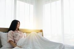 Portait усмехаясь дамы в розовом бодрствовании пижамы вверх по протягивать радушный свет утра на кровати стоковые фото