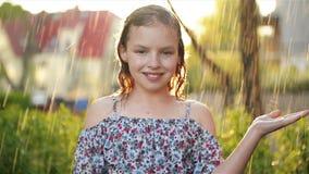 Portait av den förtjusande lilla flickan Hon spelar lyckligt i regnet på varm sommardag arkivfilmer