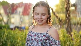 Portait av den f?rtjusande lilla flickan Hon spelar lyckligt i regnet p? varm sommardag stock video