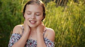 Portait av den f?rtjusande lilla flickan Hon spelar lyckligt i regnet p? varm sommardag lager videofilmer