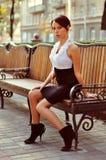 Portait av posera sitta för ung kvinna på bänken Arkivfoto