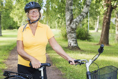 Portait of beautiful mature woman at park with a bicycle Royalty Free Stock Images