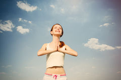 Portait of beautiful young woman doing joga on the wonderful sky Stock Image