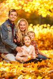 Portait of cheerful parents and children sitting in autumn park stock images