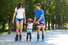 Cute baby boy and his mom learning inline skating. Portait of cute baby boy and his mom learning inline skating with skating instructor royalty free stock photos